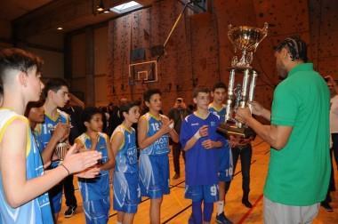 Un joueur adulte du BCM remet le trophée au capitaine de l'équipe d'Antibes Juan les Pins.