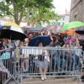 Pendant ce temps, place de la mairie, le maire offre des parapluies, aux résidents de l'Ehpad qui ont été amenés en fauteuil roulant, qui se protègent tant bien que mal du mauvais temps.