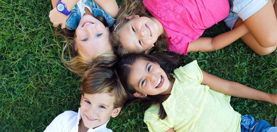 Visages d'enfants allongés en cercle sur le dos dans l'herbe